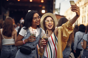 Waist up portrait of young beautiful lady in hat taking photo with smiling friend. Women holding drinks