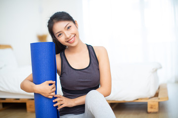 Young happy woman with yoga mat is ready for fitness