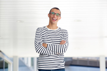confident young man with glasses smiling outside