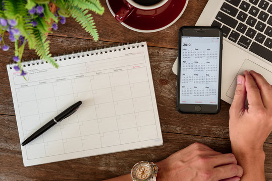 SEPTEMBER 17, 2018: Working table top with organizer for monthly planing with a pen, Macbook air, Iphone 8 plus and a cup of black coffee