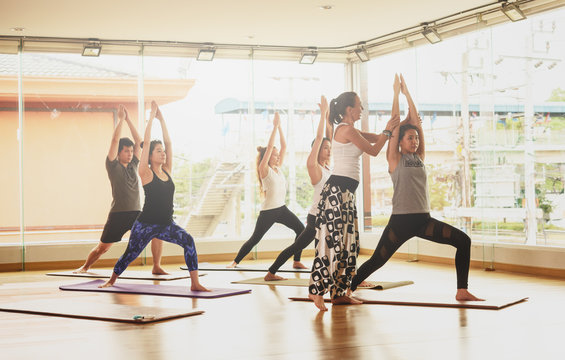 Yoga master walk among students and correct pose in a yoga class