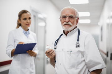 Waist up portrait of therapist in glasses holding bottle with pills while young lady in white lab coat looking at him and writing on clipboard. Focus on bearded gentleman