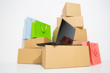 Brown different cardboard boxes arranged and shopping bags in stack and laptop.shopping online concept