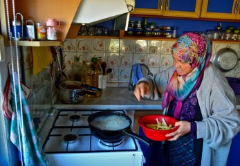 An elderly rural woman is frying potatoes in the kitchen in a small town of Turkey. Old Turkish woman.