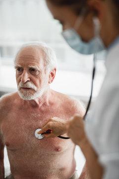 Doctor examining senior man in hospital