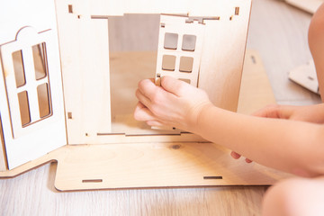 the child collects the house from the wooden designer. a concept on construction of the house.