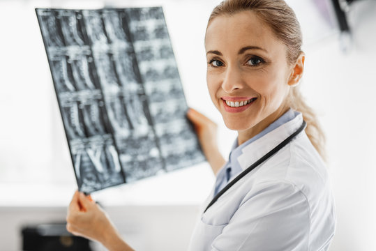 Portrait of attractive young woman in white lab coat looking at camera with smile while analyzing radiography results