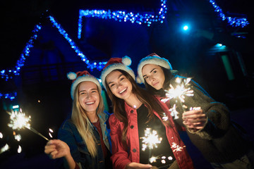 Cheerful smiling girls enjoying festive time while holding sparklers