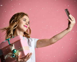 Young beautiful woman hold christmas presents gifts smiling and make selfie photo with her cellphone mobile