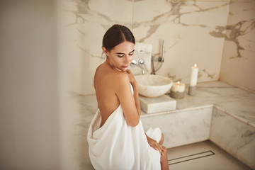 Calm pretty lady thoughtfully touching her towel while sitting in the hammam alone