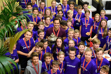 Switzerland's Roger Federer celebrates with the tournament's ball boys and girls