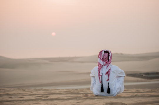 Arab man in the desert is meeting sunrise