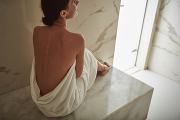 Peaceful young lady sitting in hammam and showing her back after hammam procedure