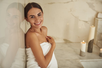 Satisfied visitor. Positive emotional young lady in white towel sitting next to the marble wall and feeling satisfied with hammam procedures