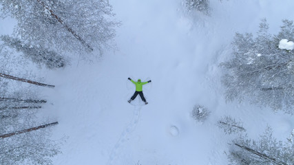 AERIAL TOP DOWN: Cheerful girl making snow angles in fresh snowy winter forest