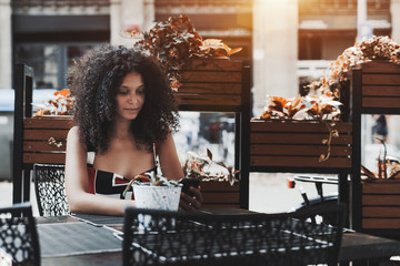 A charming caucasian girl with a curly bulky hair is chatting with her friend in a social network while waiting for a waiter in a street bar to make an order, with boxes with flowers behind her