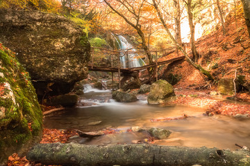 landscape with beautuful waterfall and the small bridge in foreground.
