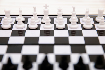 small pocket chess, plastic chess pieces placed on a chessboard on a white wooden background