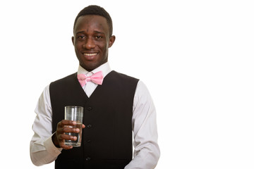 Young happy African waiter smiling and holding glass of water