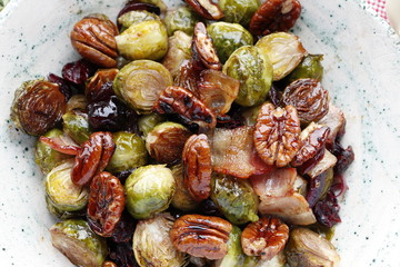 Traditional warm salad at Thanksgiving. Brussels sprouts, onions, bacon, cranberries and pecans. Close up.