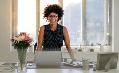 Happy businesswoman standing at her desk