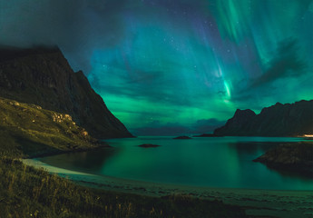 Aurora over sandy beach haukland, Kvalvika and Skagsanden with stones in Norway, Lofoten islands. Northern lights in Lofoten islands, Norway. Starry sky with polar lights. Night landscape with green