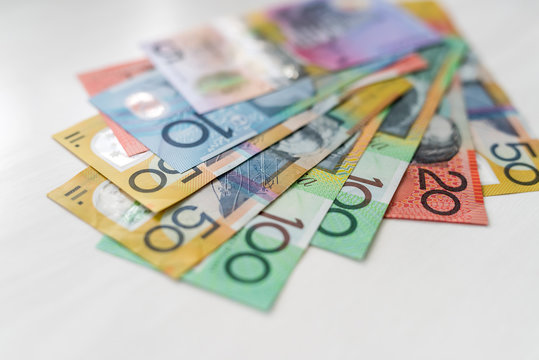 Colorful australian dollars laying on wooden table