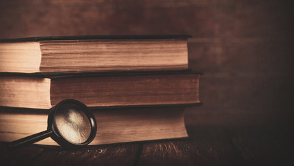 Books with loupe on wooden background. Photo in old color image style