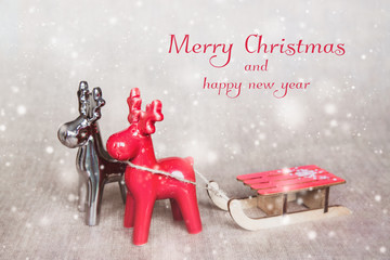 Two christmas deers with sledges. Merry Christmas - poster or postcard design.