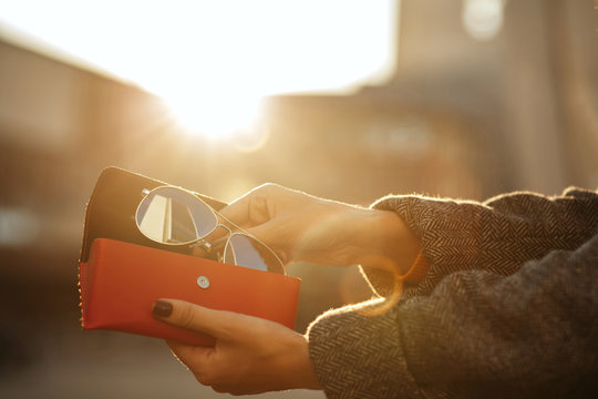 Closeup shot of woman hand opening red sunglasses case at the background of sun. Space for text