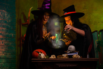 Photo of witches with pot of magic poison and steam