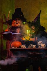Image of laughing two witches in black hats reading book of incantations on cauldron with steam