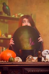 Portrait of witch hiding behind black hat