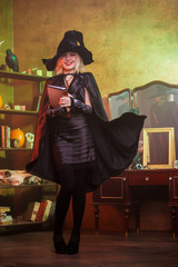Picture of witch in black hat, dress, developing cloak
