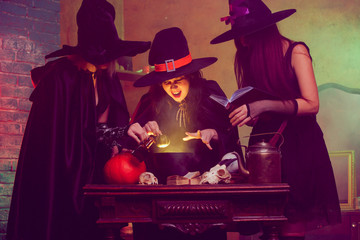 Portrait of three witches boiling potion in cauldron