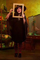 Full-length picture of smiling witch with photo frame in hat