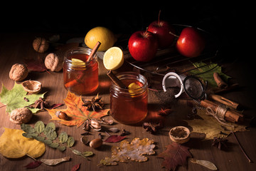 Dark wooden table with 2 glasses of tea with fall, autumn decoration and dark, black background. Colorful leaves, lemon, cinnamon, walnuts, apples, tea, walnut shells, hazelnuts, tea strainer, acorns.