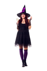 Full-length photo of cheerful witch with wine glass with wine in black dress, striped socks