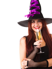 Picture of laughing witch in black hat looking at camera, with glass of champagne