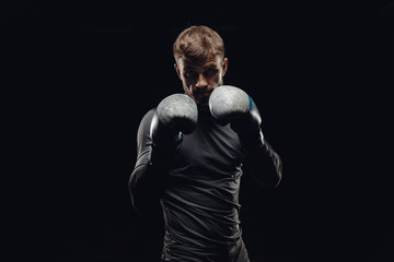 Portrait of boxer man in gloves against dark background. Concept training boxing.