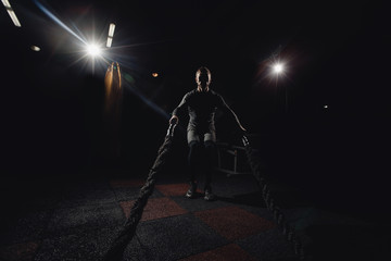 Men silhouette with battle rope in functional training fitness gym. Concept workout
