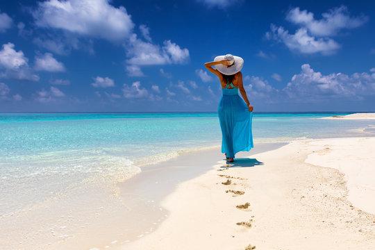 Frau im blauem Kleid läuft an einem tropischen Strand und genießt ihren Urlaub