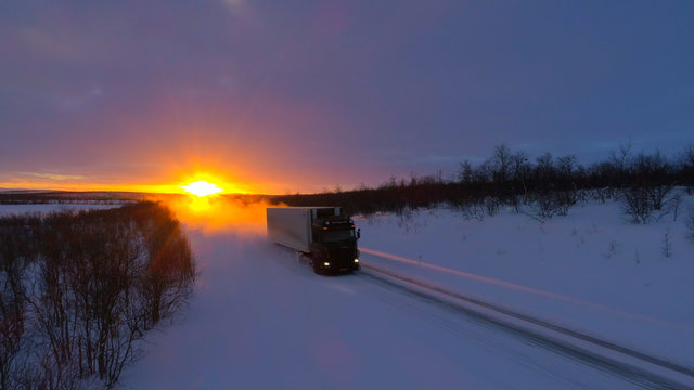 LENS FLARE: Large truck speeding down empty road through the wintry landscape.
