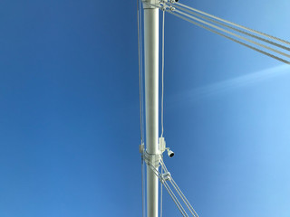 Detail of white cables and steel of suspension bridge agaisnt clear blue sky with sun ray