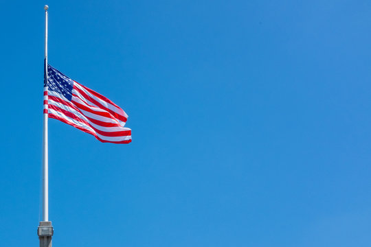 Flag of the United States of America at half staff on a clear windy day.