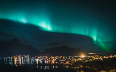 Northern Lights Aurora Borealis with classic view of the fisherman s village of Reine near Hamnoy in Norway, Lofoten islands. This shot is powered by a wonderful Northern Lights show.