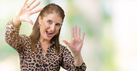 Beautiful middle age mature rich woman wearing leopard dress over isolated background Smiling doing frame using hands palms and fingers, camera perspective