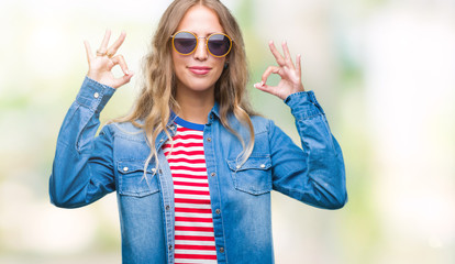 Beautiful young blonde woman wearing sunglasses over isolated background relax and smiling with eyes closed doing meditation gesture with fingers. Yoga concept.