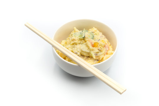 Japanese Potato Salad With Cucumbers, Carrots, and Onion isolated on the white and wooden chopsticks