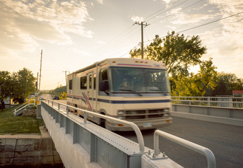 Motorhome driving across a bridge at dusk